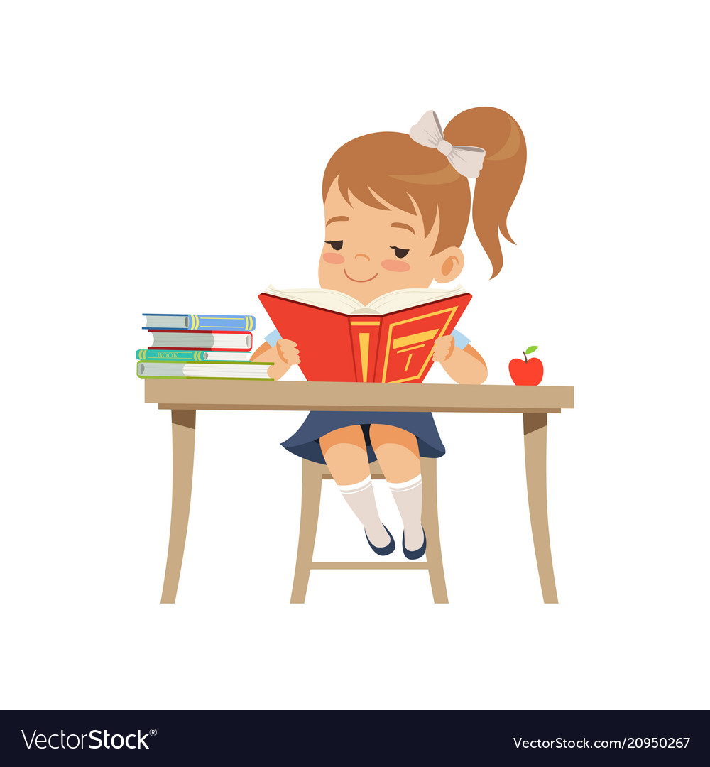 Cute girl sitting at the desk and reading a book