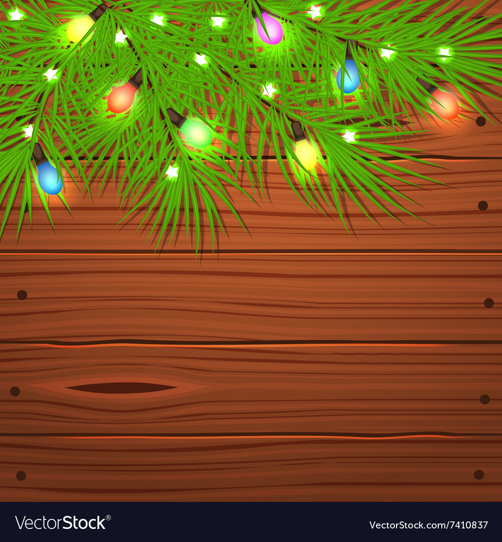Christmas tree branches and light bulb on wooden
