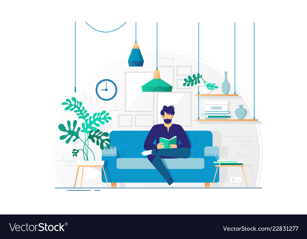 Young man with beard reading book sitting on couch