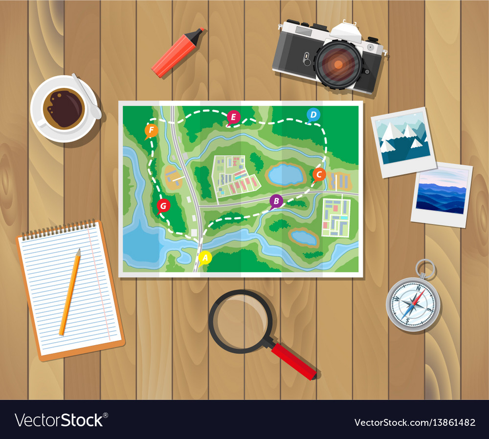 Wooden table with paper map planning trip