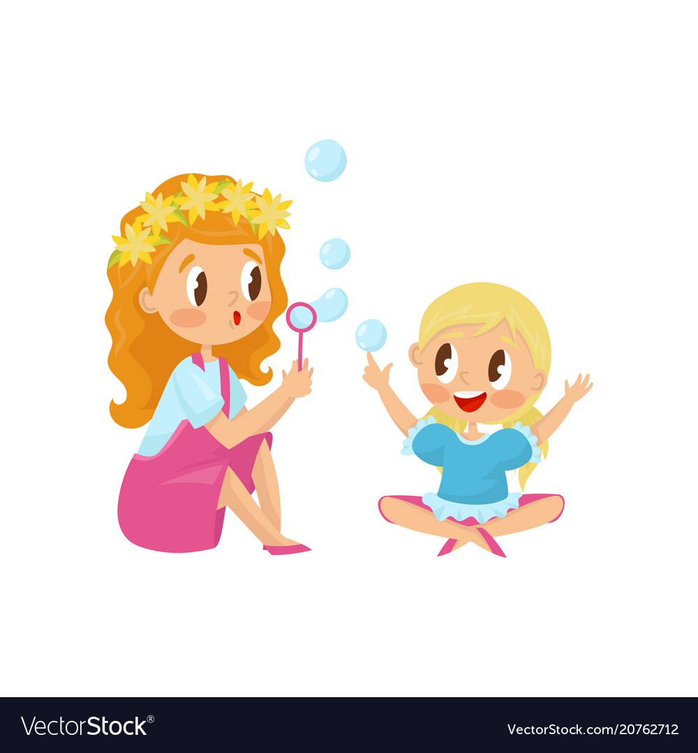 Cute girl blowing soap bubbles with her little