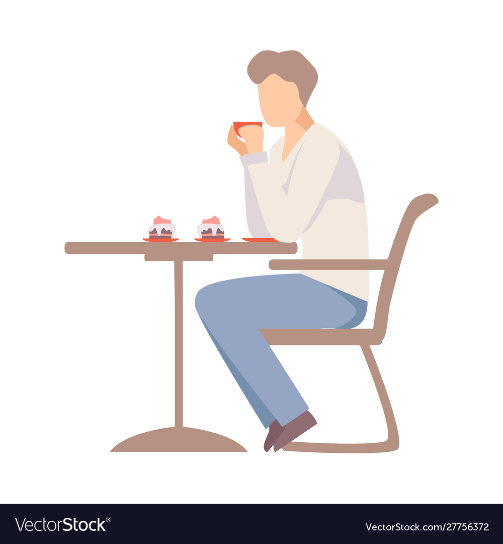 Man drinks coffee at a table in a cafe