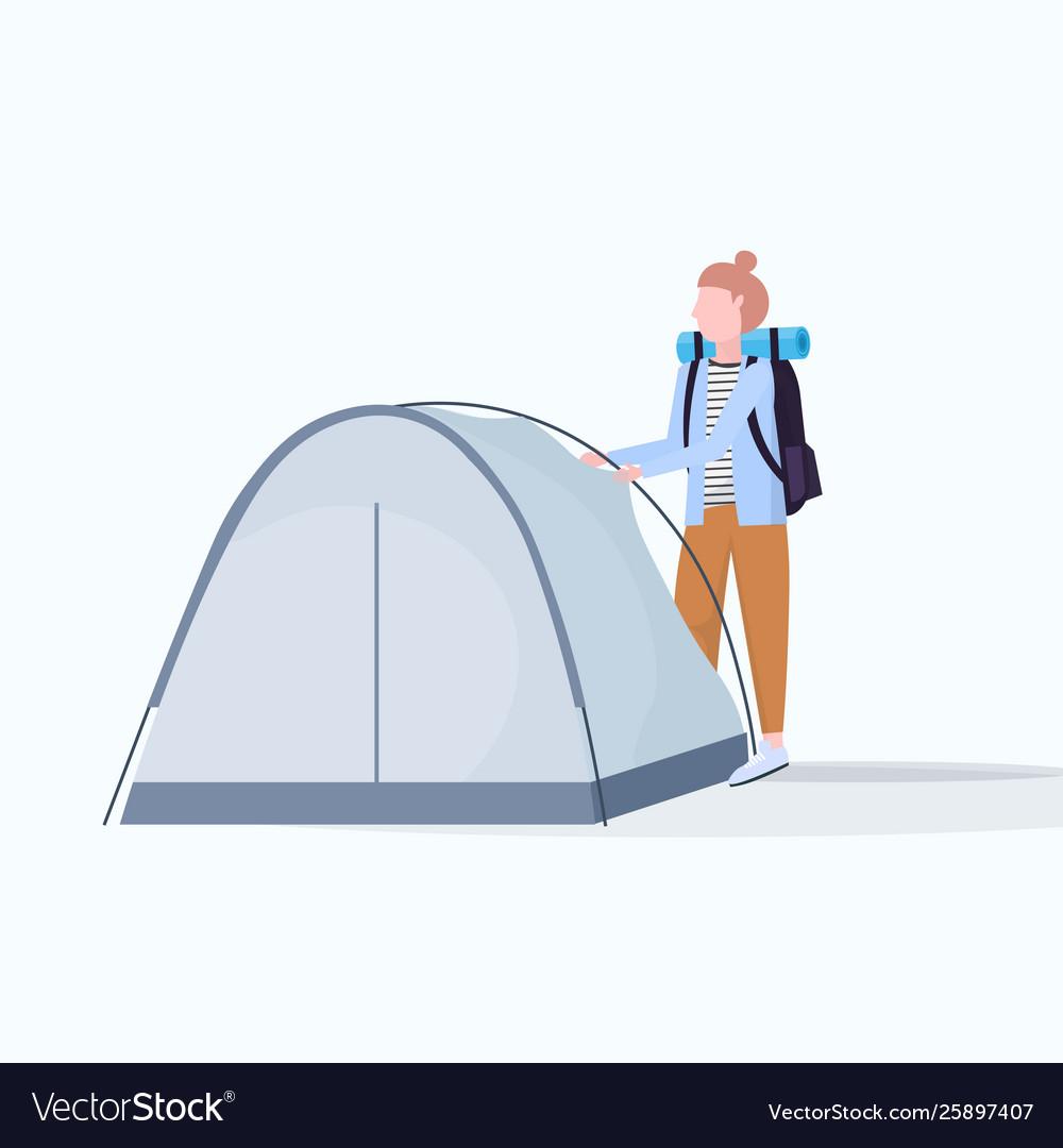 Woman hiker camper installing a tent preparing