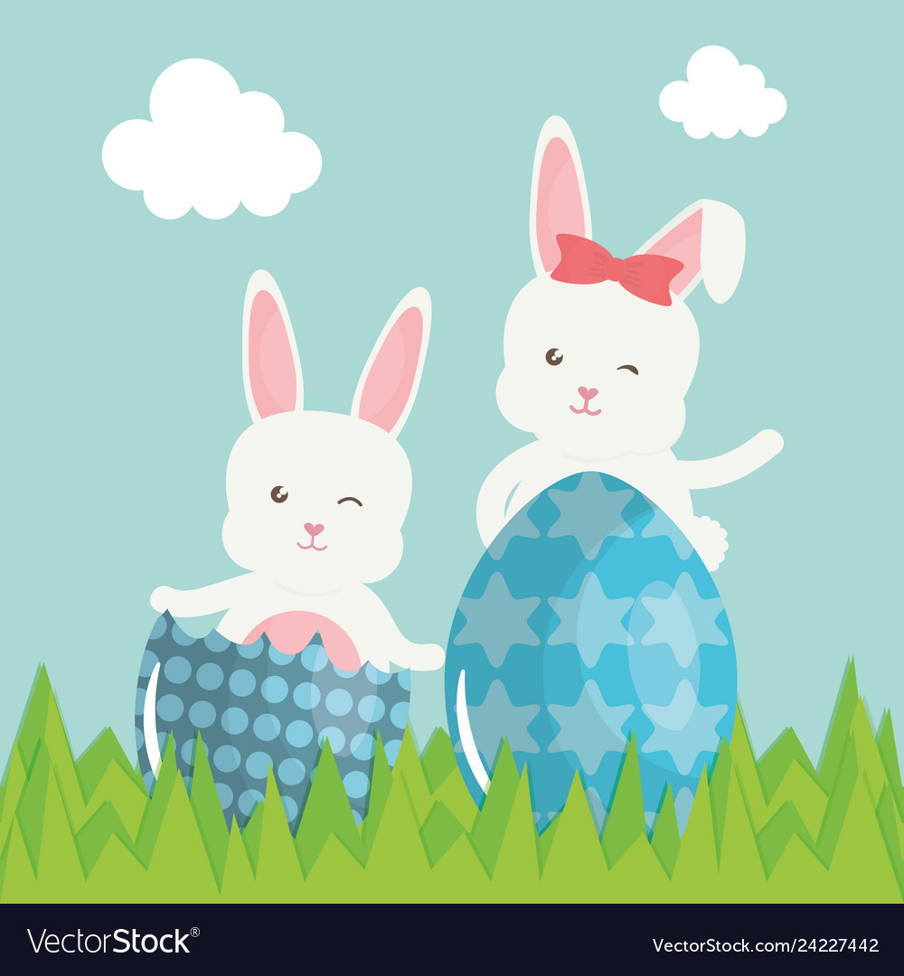 Cute rabbits with easter eggs painted in the field