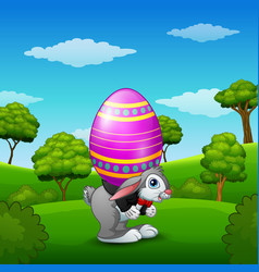 Cartoon easter bunny carrying easter eggs in the p vector