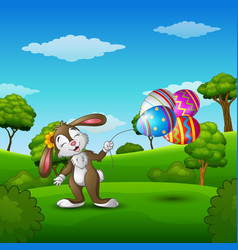 Easter bunny holding easter eggs balloons in the p vector