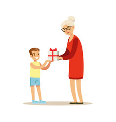 Grandmother giving gift box to her happy grandson vector