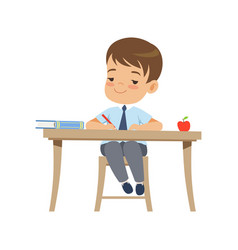 Cute boy sitting at the desk and writing vector