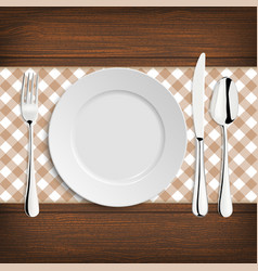 Plate with spoon khife and fork on a wood table vector