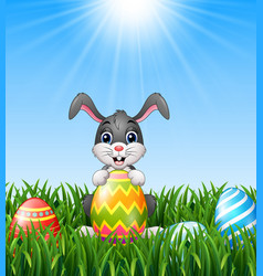 cartoon bunny holding easter eggs in the grass vector image