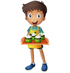A young boy holding a tray with cupcakes vector image