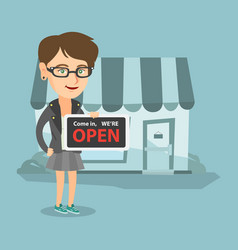 Young caucasian shop owner holding open signboard vector