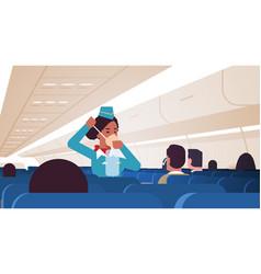 stewardess explaining for passengers how to use vector image