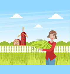 Girl farmer standing with armful fresh grass on vector