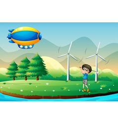 A boy playing golf in the field with windmills vector image