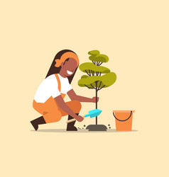 Female farmer planting young tree african american vector