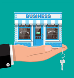 Hand holding shop or commercial property with key vector