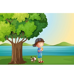 A young boy and his pet under the tree vector image