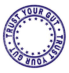 Grunge textured trust your gut round stamp seal vector
