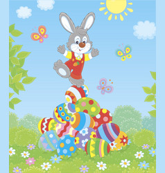 little easter bunny on a pile of decorated eggs vector image