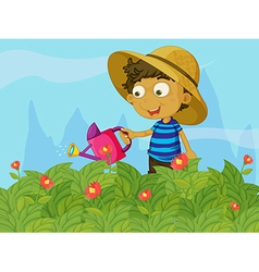 A boy watering the plants in a garden vector image