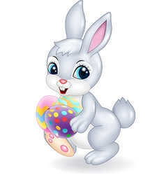 Cartoon Easter bunny holding colourful Easter eggs vector image vector image