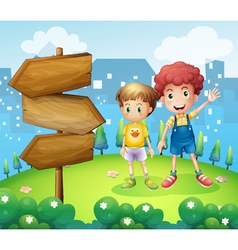 The wooden arrow beside the two young boys vector image