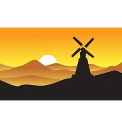 Silhouette of windmill with mountain backgrounds vector image