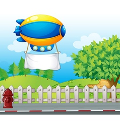 An airship with a banner near the road vector image vector image