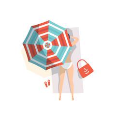 young woman sunbathing on beach under umbrella vector image