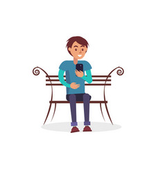 young guy sits on wooden bench and uses smartphone vector image
