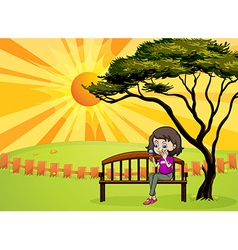 A girl in the park sitting in the wooden bench vector image