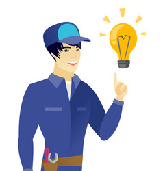 young asian mechanic pointing at idea light bulb vector image vector image