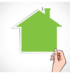 Green home icon in hand vector