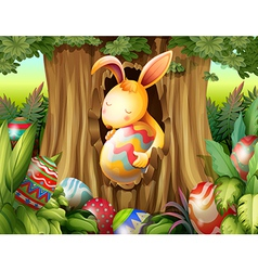 A rabbit inside the hole of a tree surrounded with vector image