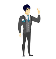 Asian groom showing the victory gesture vector