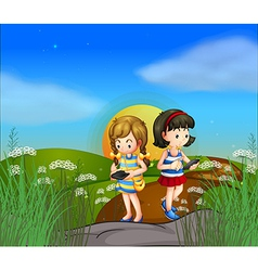 Two girls at the hilltop using their cellphones vector image vector image