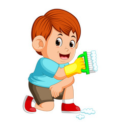 boy sitting and holding the green brush vector image