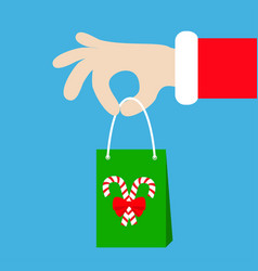 santa claus hand holding gift shopping paper bag vector image