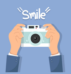 Hand holding camera with smile vector