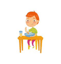 cute red-haired boy sitting at table and eating vector image