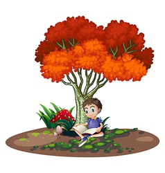 A boy reading under the tree vector image