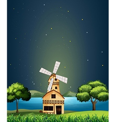 A wooden barnhouse at the river with a windmill vector
