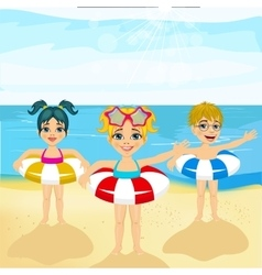 Children with inflatable rings standing on beach vector
