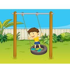 A boy swings on a wheel vector image vector image