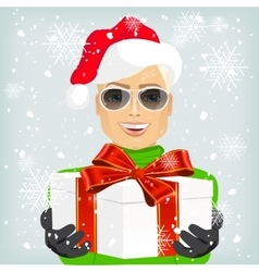 Young man wearing a santa hat offering a gift vector image
