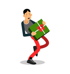 young smiling man carrying a heavy green gift box vector image