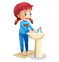 A cute little girl washing her face vector