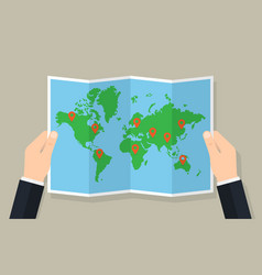 Hands hold folded paper map of world with markers vector