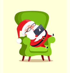 Santa claus sit in big armchair with modern tablet vector